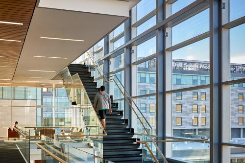 Dell Medical School Heath Learning Building interior view of stairs and large glass exterior sides