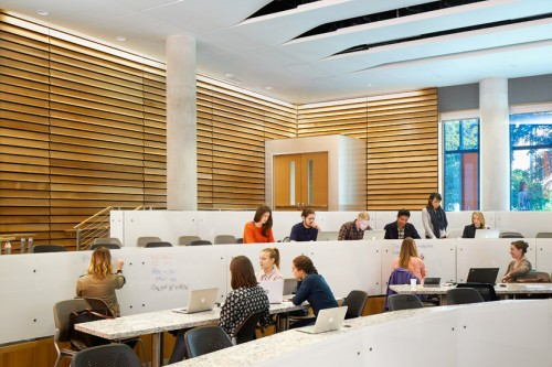 Dell Medical School Health Learning Building (HLB) interior team based learning lecture room with louvered warm wood paneled siding and open ceiling slats